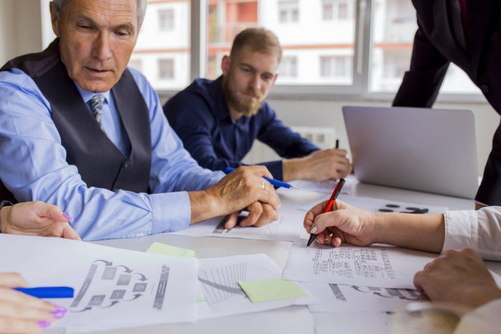 Equipe e chefe analisando resultados do ERP de gestão.