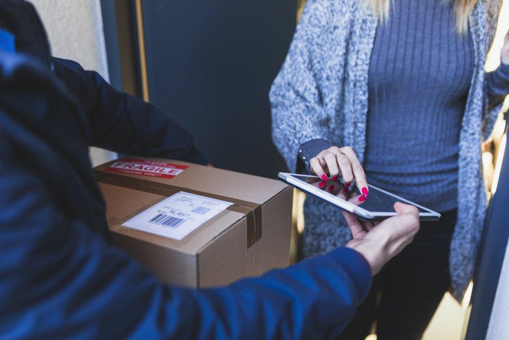 Benefícios da gestão de estoque: cliente recebendo seu pedido na porta de casa.
