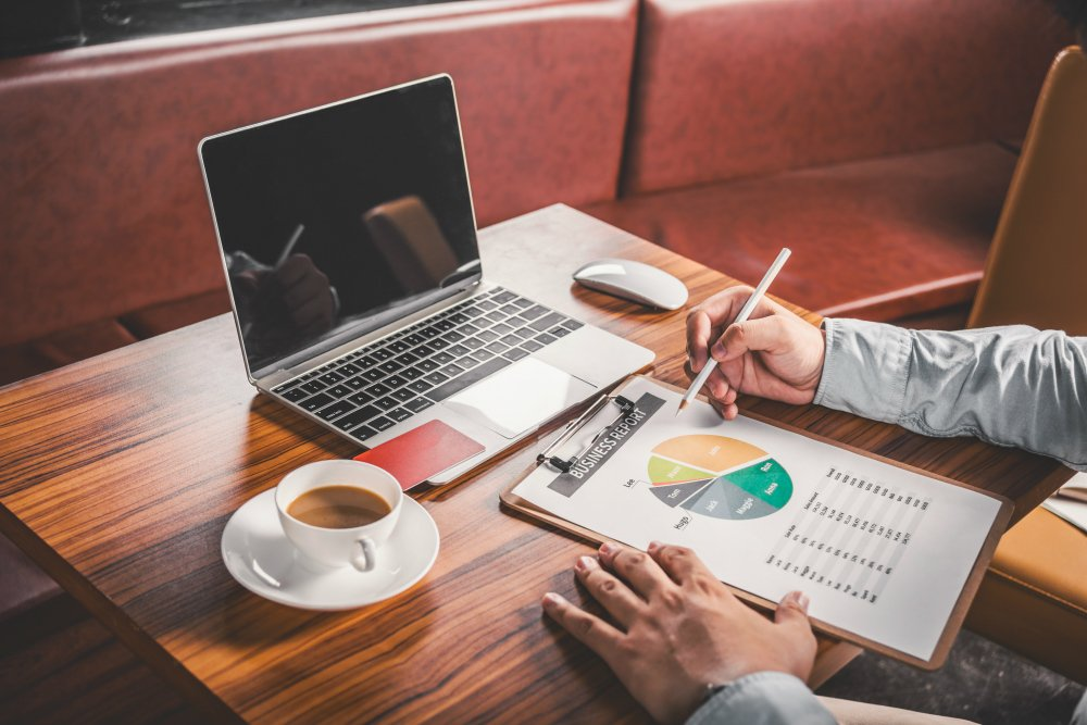 Benefícios da gestão de estoque: gestor analisando indicadores de redução de custos em frente ao computador.