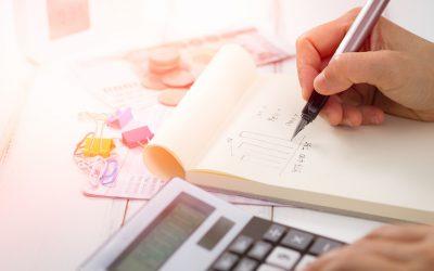 erros financeiros - mão fazendo conta em bloco de papel com a calculadora do lado.