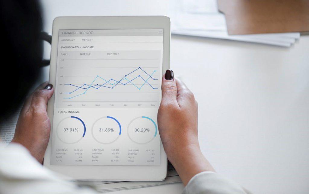 erros financeiros - mulher observando gráfico em sistema de gestão no tablet