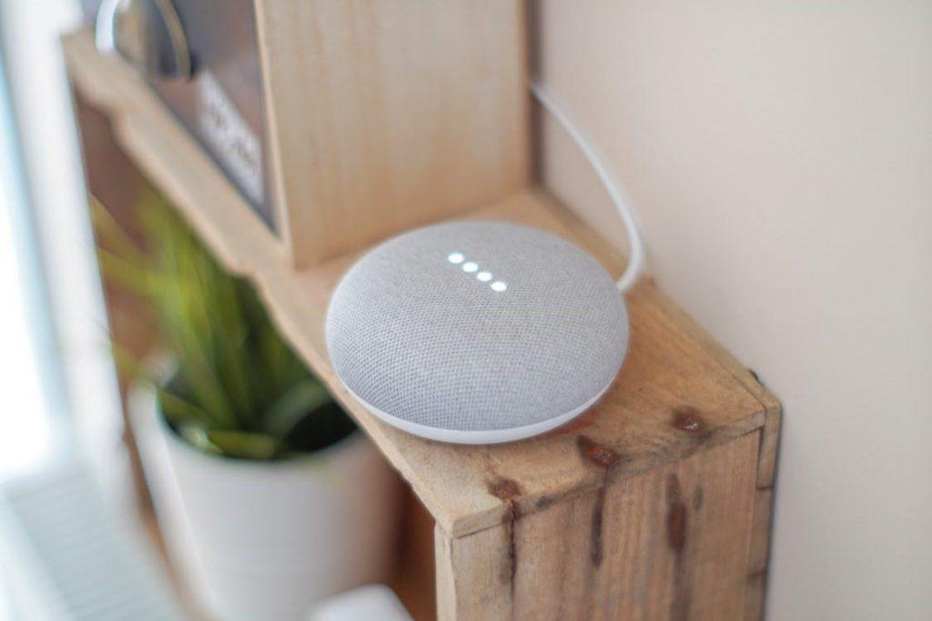 Inteligência Artificial: imagem de um aparelho eletrônico de assistência virtual, representando Google Home e Alexa, sobre cômodo.