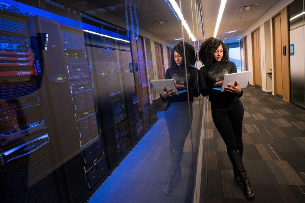 Inteligência Artificial: mulher segurando um notebook, encostada no vidro da sala de servidores, representando a união entre inteligência humana e das máquinas.