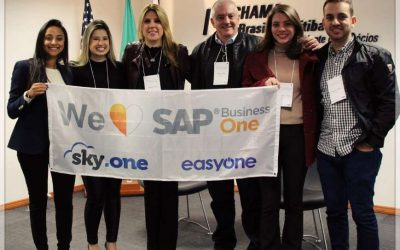 Evento de tecnologia - consultoria de SAP reunida segurando a bandeira do SAP B1